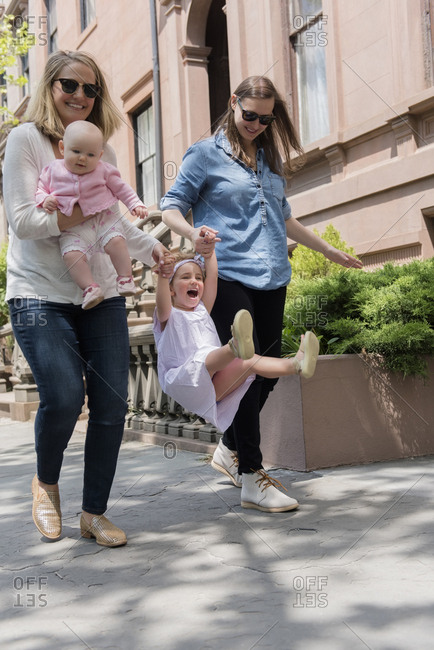 Caucasian mothers swinging daughter on city sidewalk