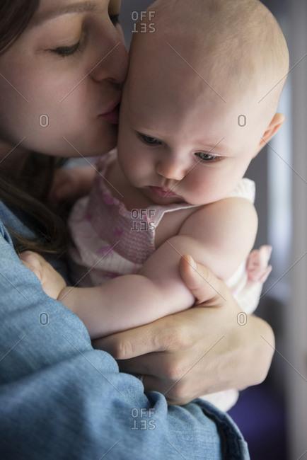 Caucasian mother kissing cheek of baby daughter