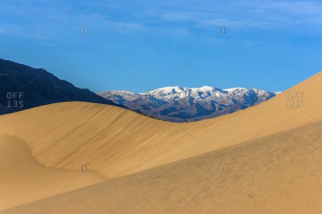 Sand dunes near snowy mountain range