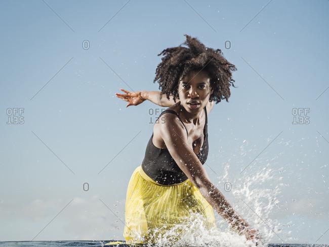 Black woman splashing in water