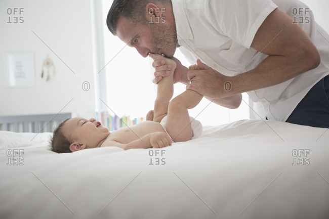 Father kissing feet of baby son on bed