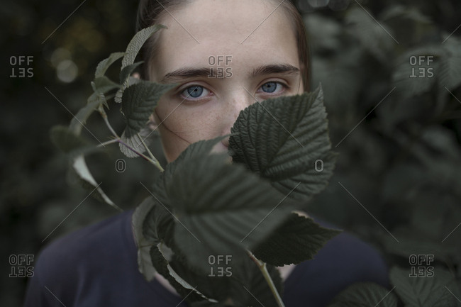 Face of Caucasian teenage girl behind leaves