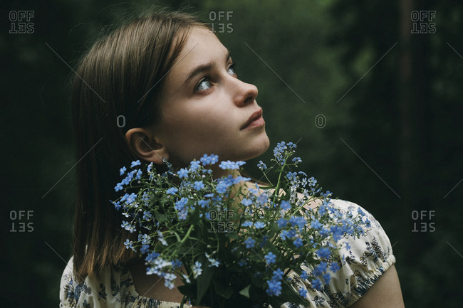 Caucasian woman holding flowers and looking up