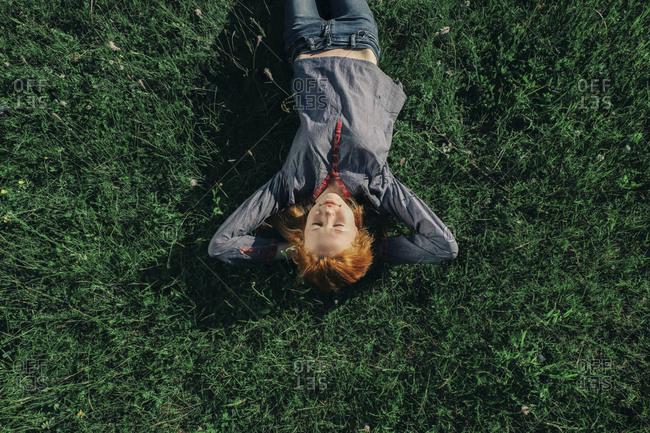 Caucasian teenage girl laying in grass