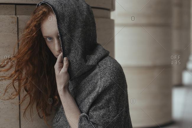 Caucasian woman hiding face behind hood