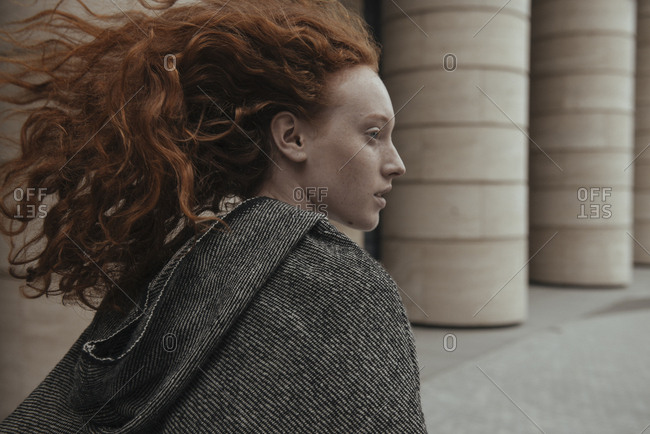 Wind blowing hair of Caucasian woman near pillars