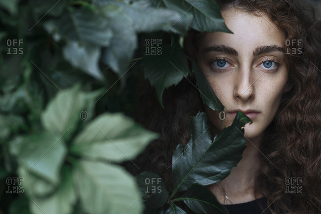 Portrait of serious Caucasian woman behind leaves