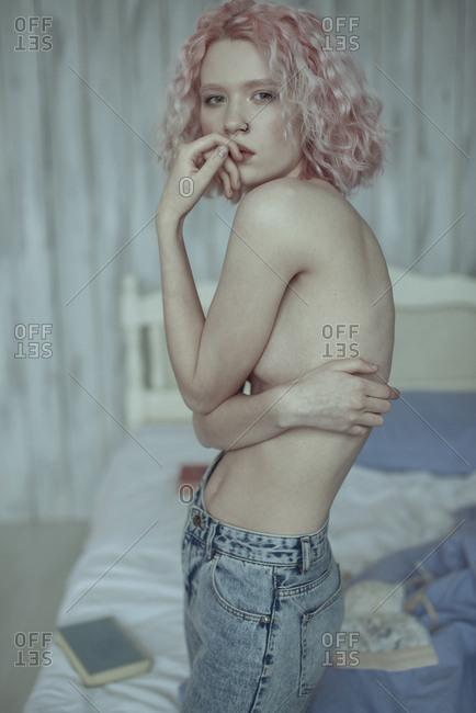 Portrait of pensive topless Caucasian woman in bedroom