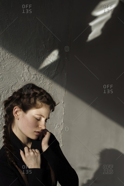 Shadow on wall over pensive Caucasian woman