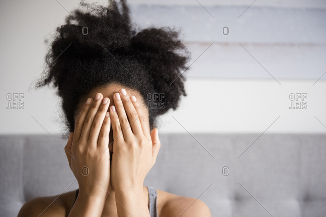 African American woman covering face with hands