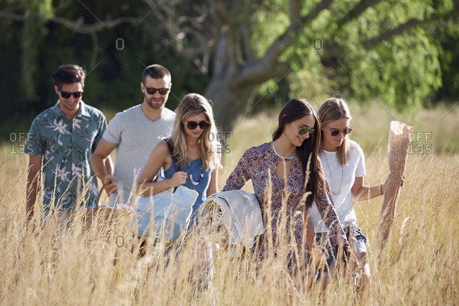 Group of friends holding blankets and food walking in field to have a picnic