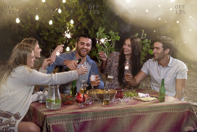 Group of friends having at a house garden party with champagne and sparklers