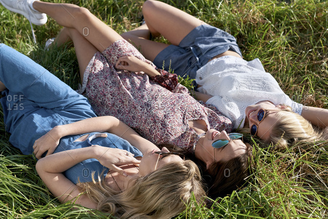 Girlfriends lying on long grass chatting and enjoying the sunshine