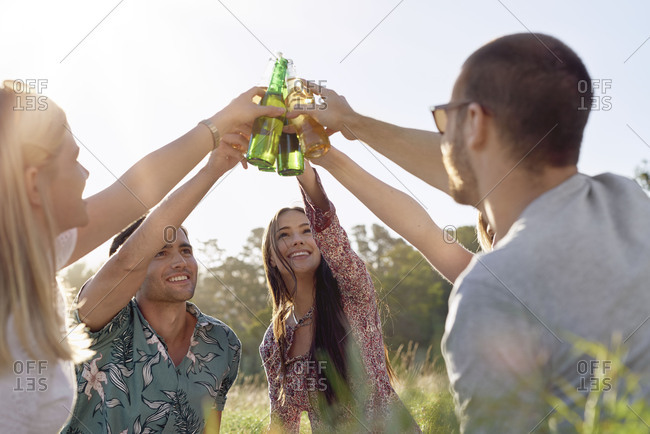 Attractive woman holding beer bottle up for toast with friends at picnic