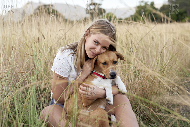 Portrait of happy woman in a meadow with pet dog
