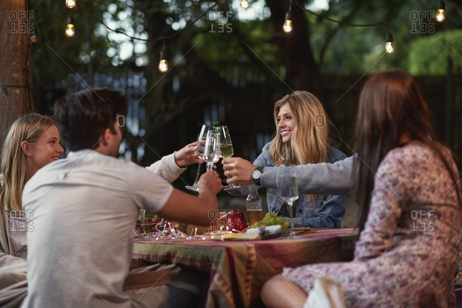 Beautiful woman holding wine glass up for cheers toast with friends at a casual garden party