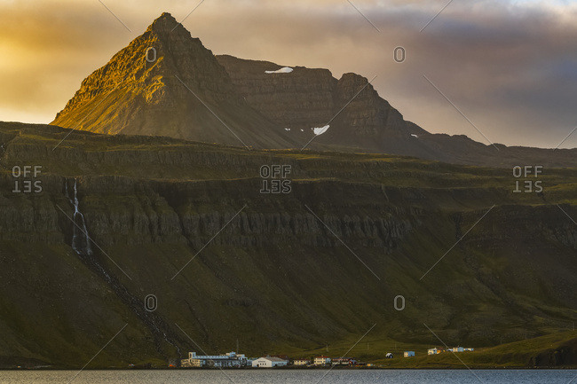 The Tiny Fishing Village Of Djupavik Is Nestled At The Base Of The Cliffs And Waterfall Along The Strandir Coast; West Fjords, Iceland
