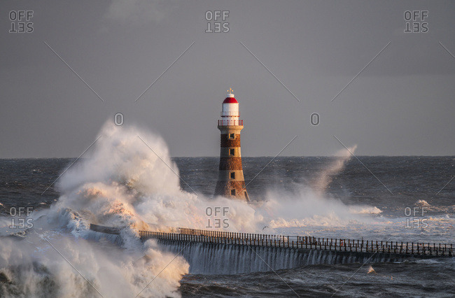 Waves Splashing Against Roker Lighthouse At The End Of A Pier; Sunderland, Tyne And Wear, England