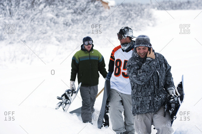 Three Snowboarders Walking Up A Trail In Deep Snow With Their Snowboards, One Snowboarder Talking On A Cell Phone; Alaska, United States Of America