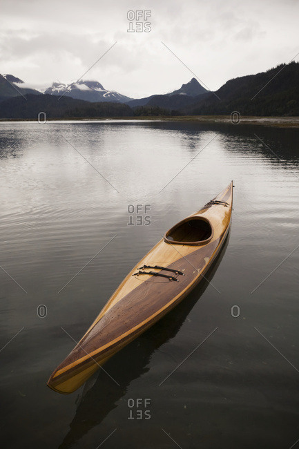 A Wooden Kayak Sits On Tranquil Water With A View Of The Mountains In The Background, Kachemak Bay State Park; Alaska, United States Of America