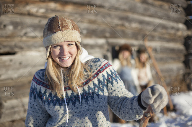 Portrait Of A Young Woman Wearing A Hat And Sweater By A Log Cabin In Winter; Homer, Alaska, United States Of America