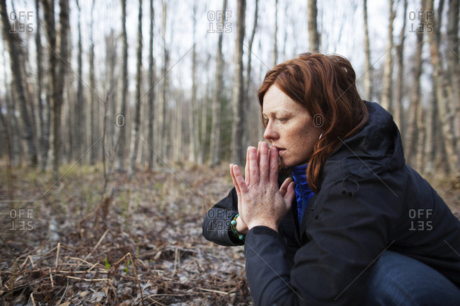 A Woman With Red Hair Crouches On A Forest Floor With Her Hands Pressed Together; Alaska, United States Of America
