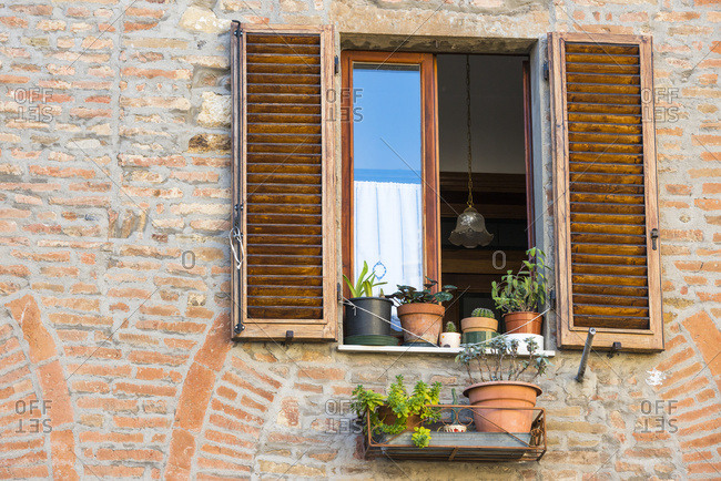 Close View Of A Montepulciano Brick House Facade With Opened Window, Flowerpots And Latticed Sun Blinds; Tuscany, Italy