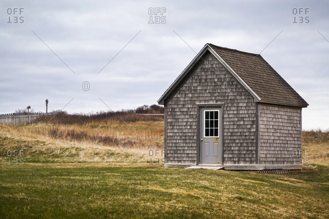 A Wooden Shed With A Single Door Along A Path And Grass Field Under A Cloudy Sky; Prince Edward Island, Canada