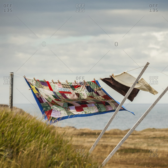 A patchwork blanket and pillow cases hanging on a clothesline with the Atlantic ocean in the background; Newfoundland, Canada