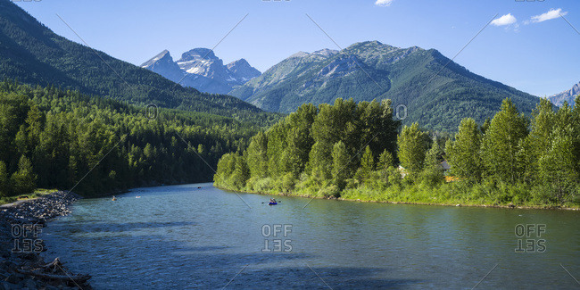 People canoeing down the Elk River with the rugged Canadian Rockies in the distance; Sparwood, British Columbia, Canada