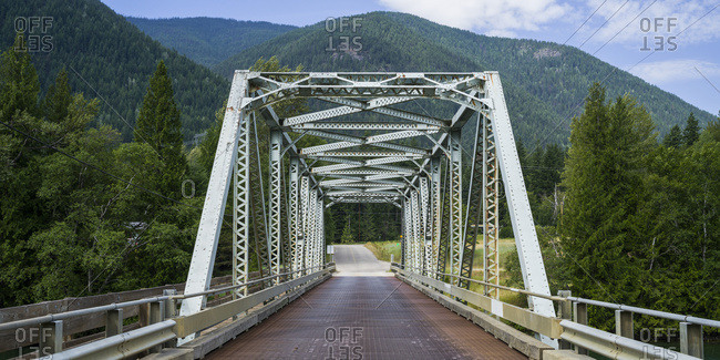 A road bridge over the Kootenay River with forests covering the Rocky mountains; British Columbia, Canada
