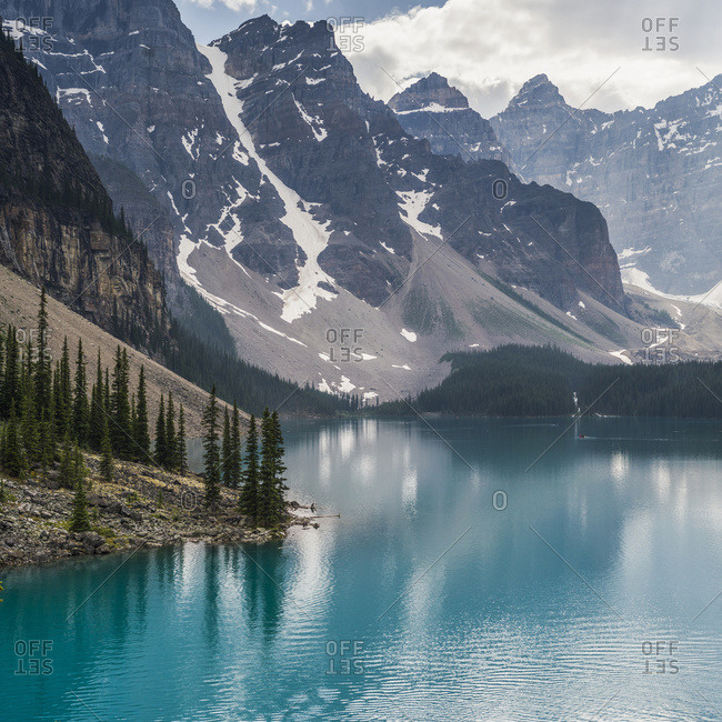 The stunning blue water of Moraine Lake with snow on the rugged mountains in Banff National Park; Lake Louise, Alberta, Canada