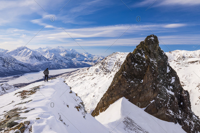 A man walks along a ridge near a large rock outcropping in the eastern Alaska Range near the Richardson Highway; Alaska, United States of America