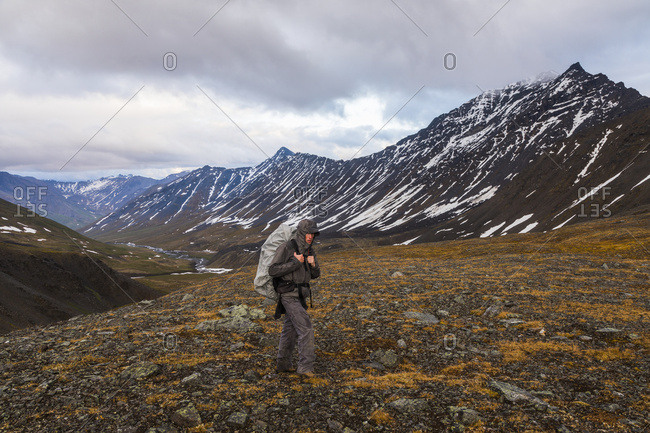 A backpacker ascends a pass during rainy weather in the Brooks Range; Alaska, United States of America