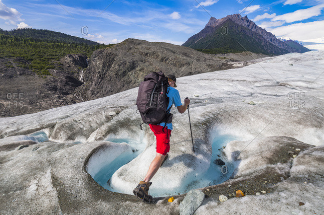 A backpacker crosses a stream on the surface of Root Glacier in Wrangell-St. Elias National Park. Donoho Peak is in the background; Alaska, United States of America