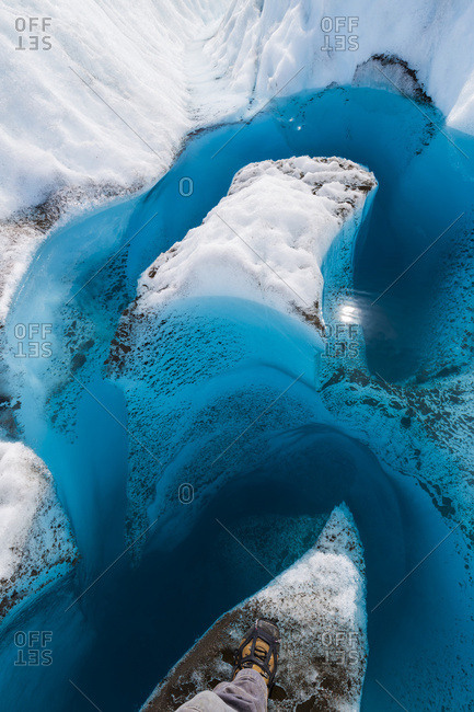 A hiker's boot showing the point of view looking down into the deep, blue meltwater of a glacier in Wrangell-St. Elias National Park; Alaska, United States of America
