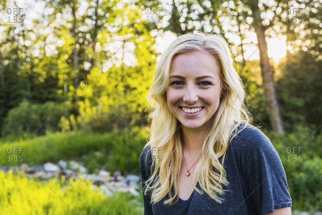Portrait of a young woman with long blond hair in a park in autumn; Edmonton, Alberta, Canada