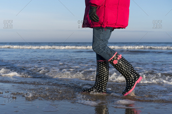 A woman in a red coat and rubber boots walks in the shallow water along the shore with the blue sky and ocean; Bamburgh, Northumberland, England