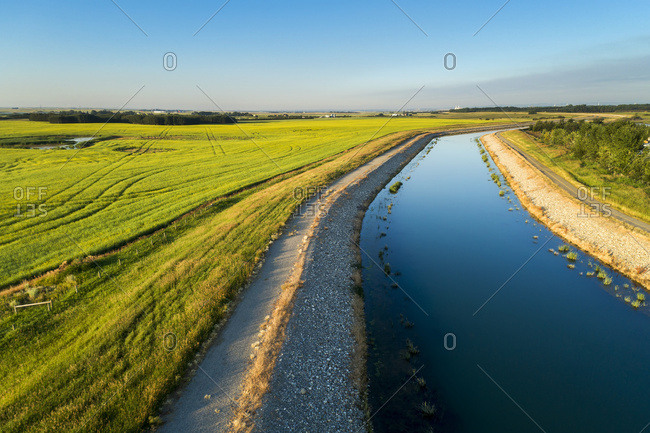 An irrigation canal with a path running alongside it and blue sky, East of Calgary; Alberta, Canada