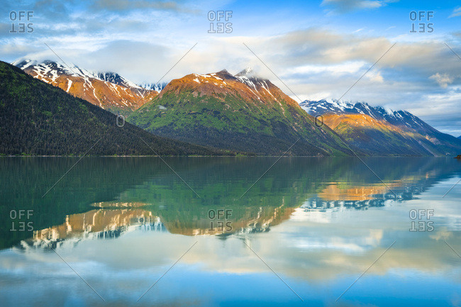 Black Mountain and Sleeping Sister Mountain in Kenai Mountains reflect on Kenai Lake at sunrise, alpenglow on the peaks. Chugach National Forest, South-central Alaska; Alaska, United States of America