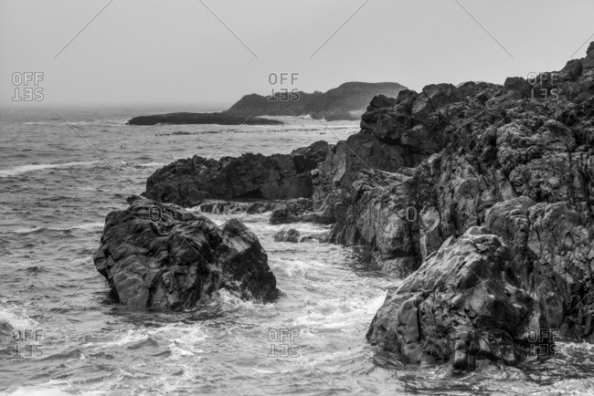 Rugged rocks line the coast at Chesterman Beach with clouds and mist obscuring the horizon, Pacific Rim, Vancouver Island; British Columbia, Canada
