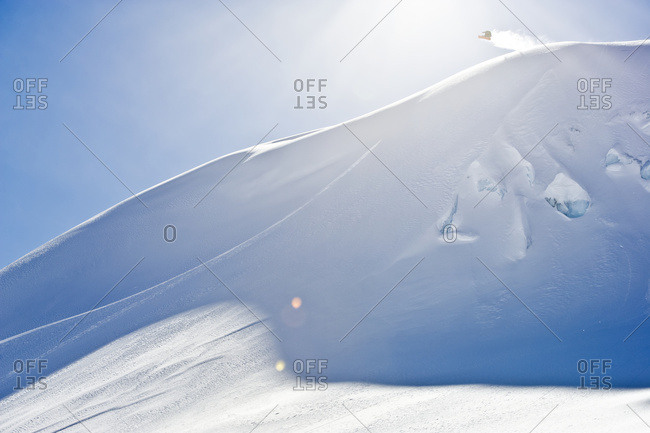 A professional, freeriding snowboarder in mid-air on a snowy slope against a blue sky; British Columbia, Canada