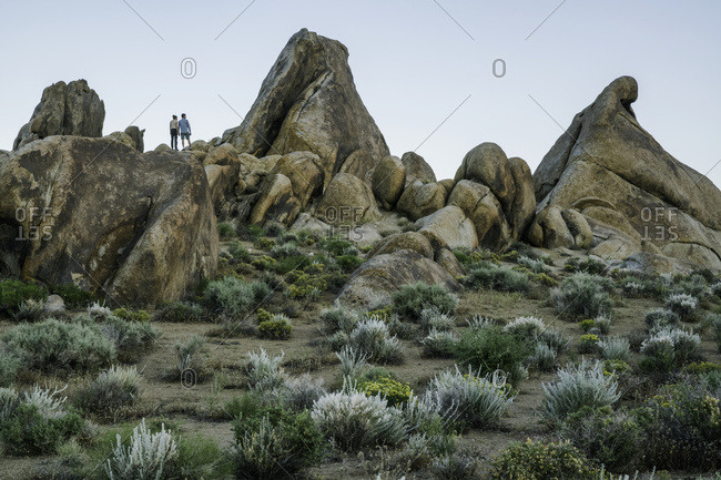 Couple standing on rocks of the Alabama Hills after sunset; California, United States of America