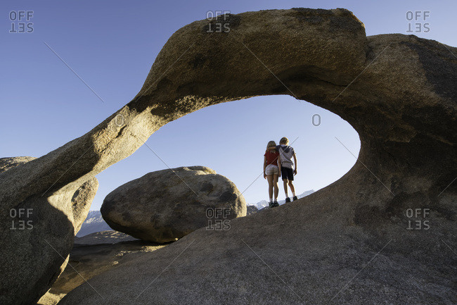 Young children standing under a natural rock arch, Alabama Hills; California, United States of America