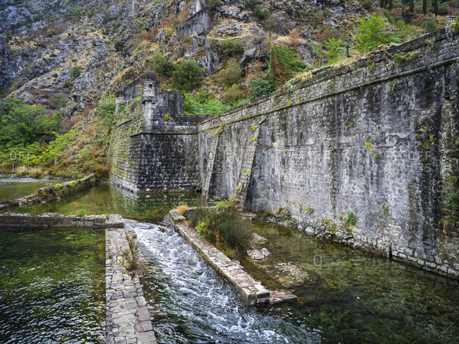 A worn stone wall with cascading water along the Bay of Kotor; Kotor, Montenegro