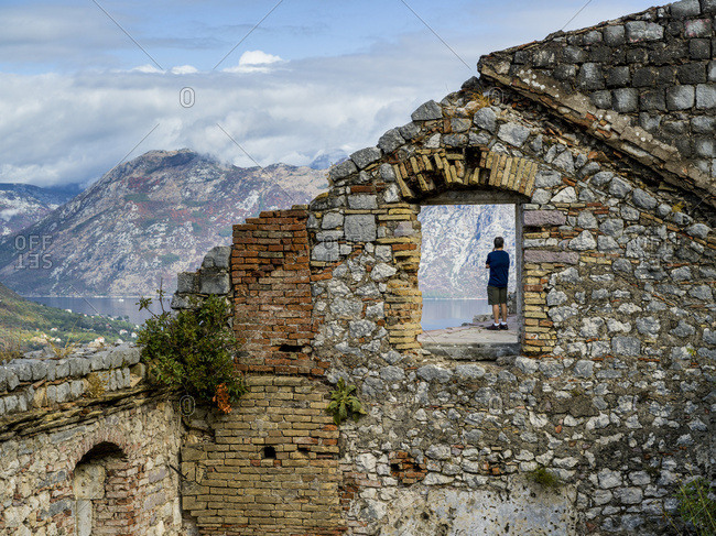A male tourist standing at Kotor's Castle of San Giovanni looking out to the water below; Kotor, Montenegro