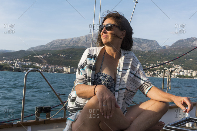 A woman sits on the deck of a sailboat with windswept hair looking out along the coast of Montenegro; Montenegro