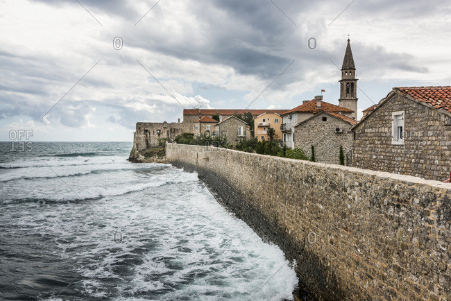 A stone wall lining the shoreline with buildings and a church tower; Budva, Opstina Budva, Montenegro