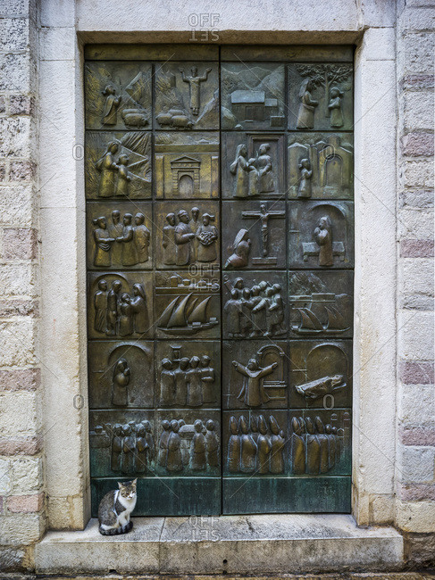 A metal door with pictograms placed in squares over the surface, and a cat sitting on the step; Montenegro