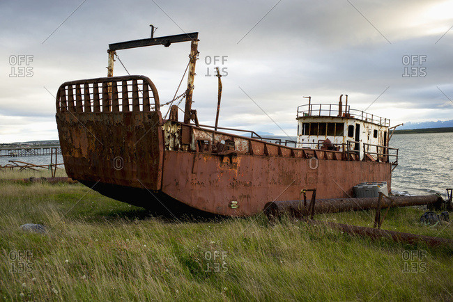 Old Fishing Boat On The Grass Shore; Natales, Magallanes And Antarctica Chilena Region, Chile
